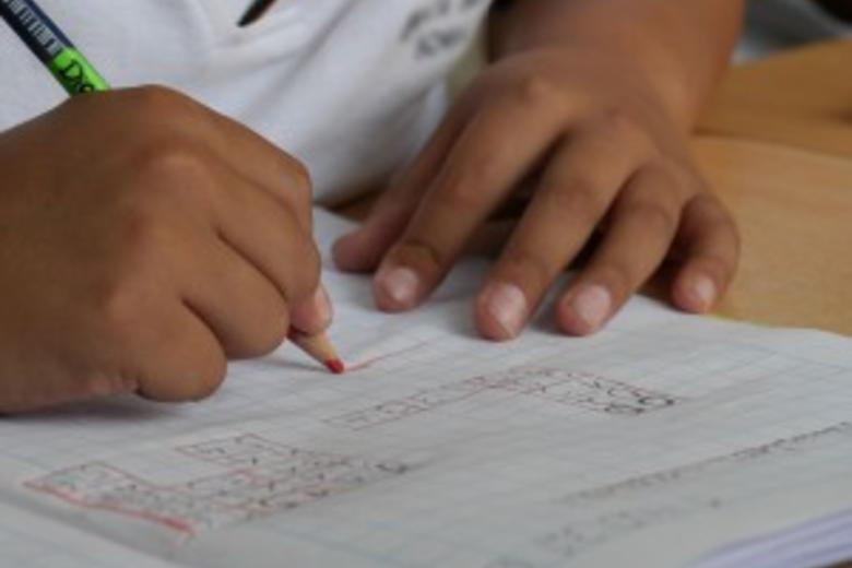 A child drawing in pencil in a notebook