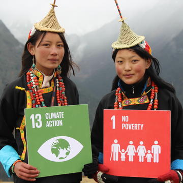 Two people holding signs which read '13 Climate Action' and '1 No Poverty'. Photo: UNDP Bhutan